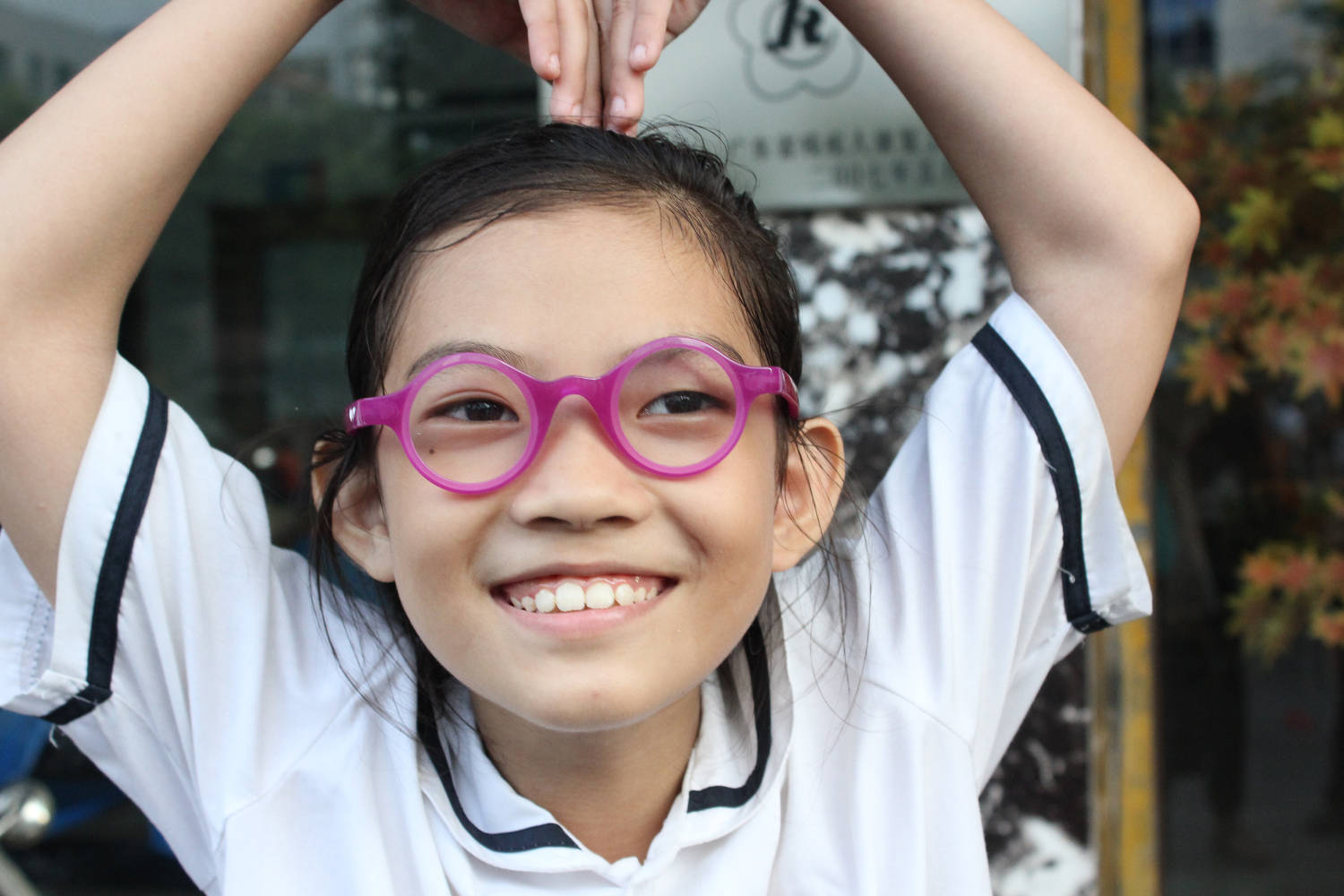 child wears pink adaptive spectacles
